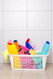 Cleaning supplies in plastic basket on tiled floor Royalty Free Stock Images