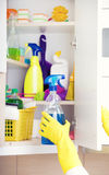 Cleaning supplies storing in pantry. Woman with safety gloves storing cleaners in pantry on the wall stock photos