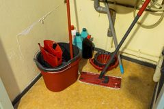 Cleaning supplies and tools arranged in storage place in a office stock image
