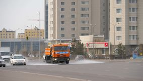 Cleaning sweeper machine. ASTANA, KHAZAKHSTAN - APRIL 18, 2018: Cleaning sweeper machine washes the city asphalt road with water spray stock footage