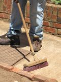 Cleaning/sweeping. Heavy duty broom and legs of a worker sweeping the garden path Royalty Free Stock Photos