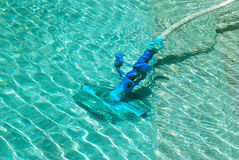 Cleaning swimming pool. Cleaner tool cleaning the ground of the swimming pool under water Stock Photos