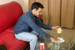 Cleaning table. Young guy cleaning glass table Royalty Free Stock Photography