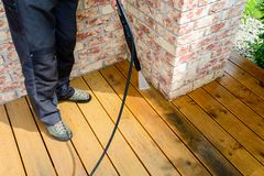 Cleaning terrace with power washer - high water pressure clean. Cleaning terrace with a power washer - high water pressure cleaner on wooden terrace surface stock photos