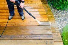 Cleaning terrace with a power washer - high water pressure clean. Er on wooden terrace surface royalty free stock image