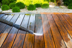 Cleaning terrace with a power washer. High water pressure cleaner on wooden terrace surface royalty free stock photography