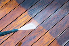 Cleaning terrace with a power washer. High water pressure cleaner on wooden terrace surface Stock Photo
