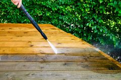 Cleaning terrace with a power washer - high water pressure clean. Er on wooden terrace surface royalty free stock photo