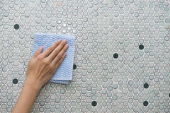 Cleaning tile wall by woman hand royalty free stock photography