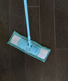 Cleaning the tiled floor with blue mop Stock Image