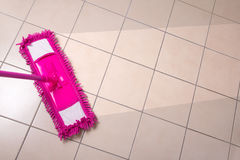 Cleaning the tiled floor with purple mop Stock Photos
