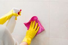 Cleaning tiles in bathroom with pink cloth. Hands with yellow rubber gloves holding detergent spray bottle and cleaning tiles in bathroom with pink cloth. Spring Stock Photography