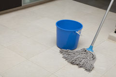 Cleaning time. Wet floor with mop and bucket of water stock photo