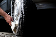 Cleaning tire in a car wash. With brush Royalty Free Stock Photography