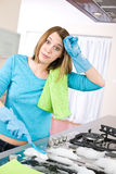 Cleaning - Tired woman cleaning stove in kitchen Royalty Free Stock Photo