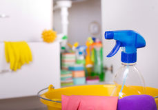 Cleaning tools in kitchen. Close up of spray bottle and cloths in bucket. Cleaning supplies and equipment stored in kitchen cabinet in background Stock Images