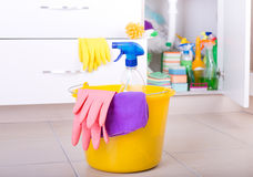 Cleaning tools on kitchen floor. Spray bottle, cloth and rubber gloves in bucket on tiled floor in kitchen. Cleaning supplies and equipment stored in cabinet in Royalty Free Stock Photos
