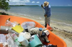 Cleaning up the beach. Woman cleans up the beach and collects the washed up garbage Stock Image