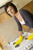 Cleaning up cooker. Young woman in yellow rubber gloves cleaning cooker. Looking at camera. Front view royalty free stock photography