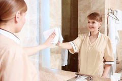 Cleaning up the mirror in room Royalty Free Stock Images