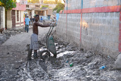 Cleaning Up Mud. September 26, 2008 - A young man uses a wheelbarrow to clean mud from his family compound after Hurricane Ike flooded the city of Gonaives Royalty Free Stock Image