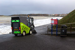 Cleaning vehicle cleaning the promenade at Ballyholme, Bangor Ireland during a gale in spite of the breaking waves. Cleaning vehicle still busy cleaning the royalty free stock photography