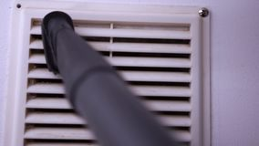 Cleaning Ventilation Grill with Vacuum Cleaner. Closeup of Cleaning Ventilation Grill with Vacuum Cleaner Pipe. Housework and Cleaning Concept stock footage