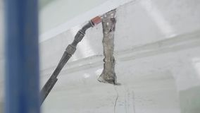 Cleaning washing process of crack in wall by using pipe with spray water tip. Cleaning and washing process, removing dust off of crack in wall by using long stock video