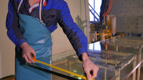Worker clean and dry the glass on manufacture. Smiling mid adult worker cleaning soap sud on glass window with squeegee Royalty Free Stock Photography