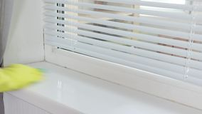 Cleaning washing window sill with a sanitary spray and a sponge by a woman`s hand in yellow rubber glove stock video