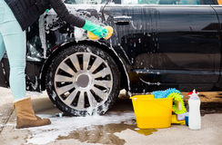 Cleaning the wheel car wash with a sponge. Woman cleaning the wheel car wash with a sponge Royalty Free Stock Image