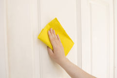 Cleaning a white door with a yellow cloth Stock Photo