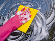Cleaning window. Female left hand in pink glove cleaning window with yellow microfibre stock photography