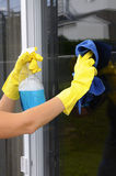 Cleaning a window. Woman polishing glass door using microfiber cloth and yellow latex gloves Royalty Free Stock Images