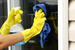 Cleaning a window. Woman polishing glass door using microfiber cloth and yellow latex gloves Stock Images