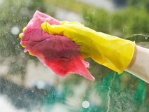 Cleaning window glass by wet rag. Hand in yellow rubber glove cleaning window glass by wet rag Stock Photo
