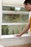 Cleaning a Window Sill with a Dust Cloth. Mature male dusting an interior window sill ledge of a screened and open home bathroom window. Man cleaning dust Stock Photos