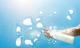 Cleaning window spray - spring cleaning concept. Male hand with white spray bottle cleans a window against blue sky. ideal for websites and magazines layouts Stock Photos