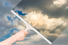 Cleaning window with squeegee to clean the sky Stock Photo
