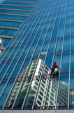 Cleaning Windows. Man cleaning windows of skyscrapper Royalty Free Stock Photo