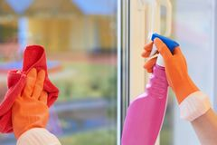 Window cleaning. Hands in gloves with a spray and a rag royalty free stock photos