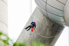 Cleaning windows service on high rise building. it is dangerous. Cleaning windows service on high rise building. The man climber or Spiderman which clean or wipe Stock Photo