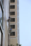 Cleaning windows on the side of a high rise building Royalty Free Stock Photography