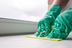 Cleaning windowsill with yellow cloth Royalty Free Stock Image