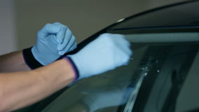 Cleaning the windshield. Cleaning windshield with gloves and small cloth