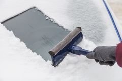 Cleaning windshield from snow with scraper Royalty Free Stock Photos