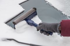 Cleaning windshield from snow with scraper Royalty Free Stock Images