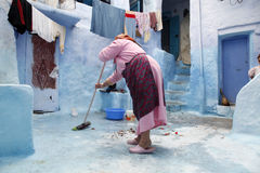 Cleaning. A woman is cleaning the backyard Royalty Free Stock Photography
