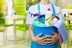 A cleaning woman is holding a bucket fulfilled with chemicals and facilities for tidying up. A cleaning woman is holding a blue bucket fulfilled with chemicals royalty free stock images