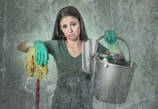 Cleaning woman housewife or house maid service cleaner girl looking tired and frustrated holding mop and washing bucket. Grunge edit portrait of sad and Royalty Free Stock Photos